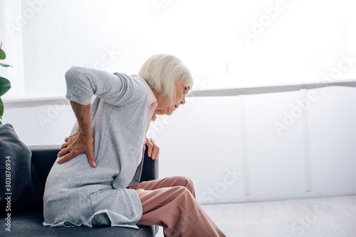 Fotografía side view of senior woman having back pain in apartment