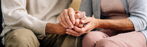 Fotografie, Obraz panoramic shot of husband and wife holding hands in apartment