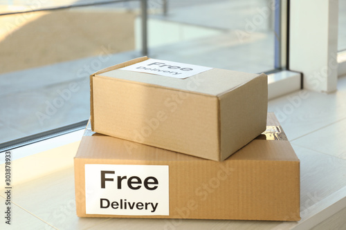 Obraz Parcels with sticker Free Delivery on window sill. Courier service - fototapety do salonu