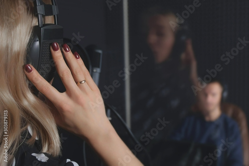 Cuadros en Lienzo Man sound engineer in studio recording song of woman professional vocalist singer singing in microphone