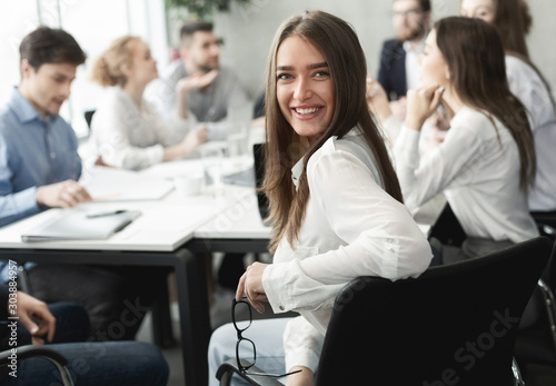 Happy business lady smiling to camera during meeting