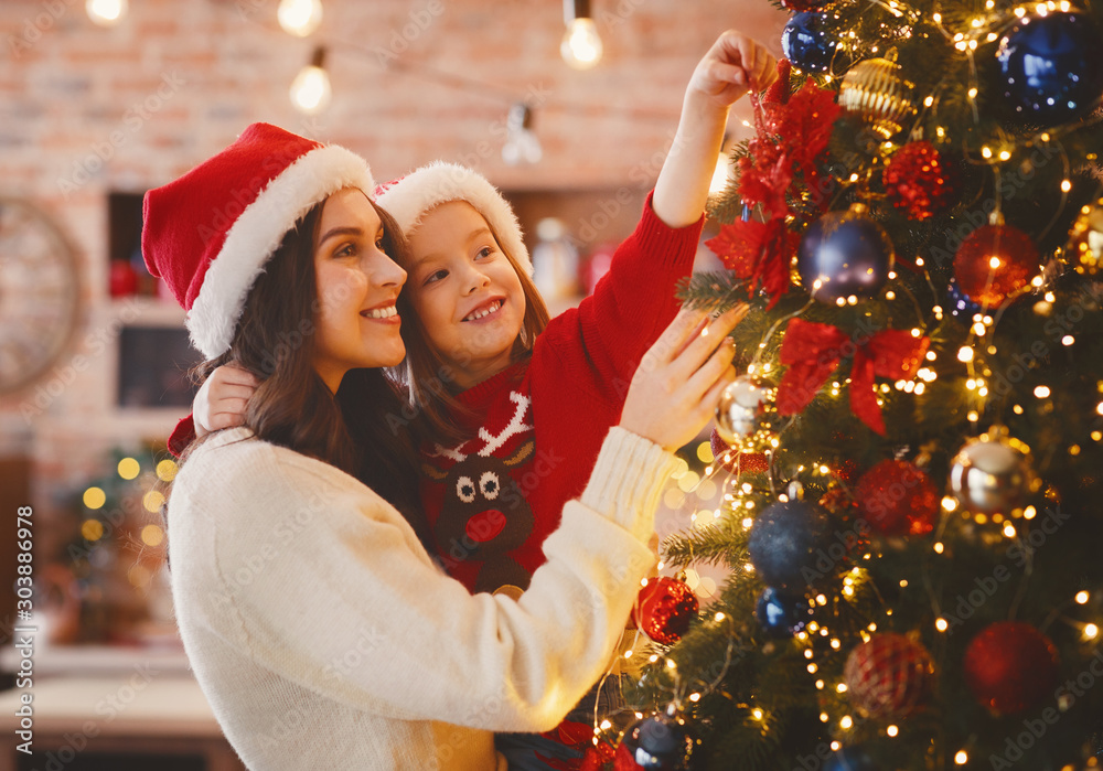 Fototapety, obrazy: Festive mother and daughter decorating Christmas tree at home