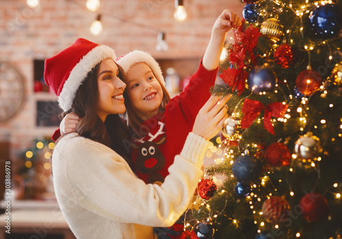 Cuadros en Lienzo  Festive mother and daughter decorating Christmas tree at home