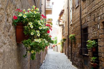 Fototapeta na wymiar A medieval italian street in Orvieto with flowers