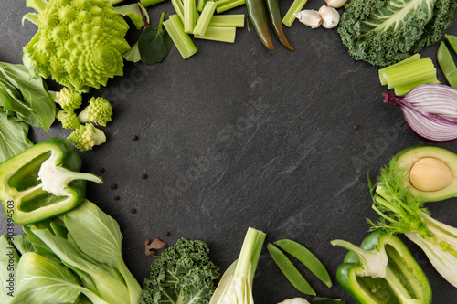 Obraz food, culinary and healthy eating concept - close up of different green vegetables and fruits on slate stone background - fototapety do salonu