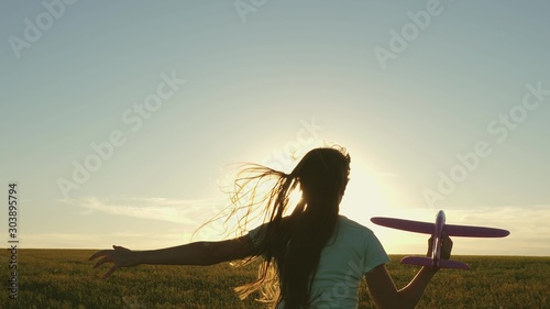 Happy girl runs with a toy airplane on a field in the sunset light Wallpaper Mural