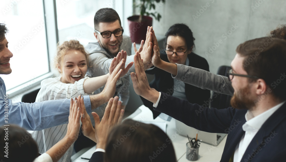 Fototapeta Motivated business team giving group high five