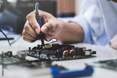 Fotografía  Close up of the hand men hold tool repairs electronics manufacturing Services, Manual Assembly Of Circuit Board Soldering