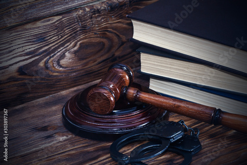 Handcuffs and a wooden gavel in front of manila folders. Canvas Print