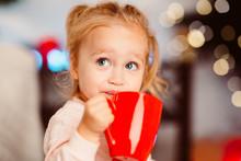 Cute Little Girl Drinking Warm...