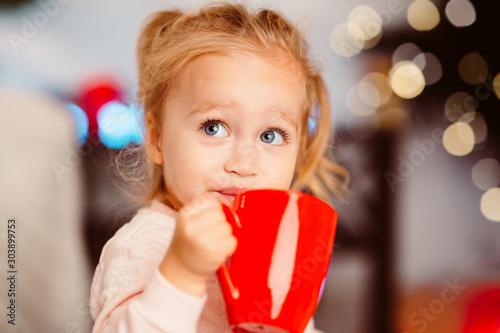 Obraz Cute little girl drinking warm cocoa sitting near Christmas tree - fototapety do salonu
