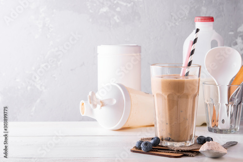 Stampa su Tela Chocolate protein shake on a white wooden background