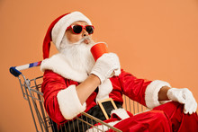 Santa Claus In Shopping Cart Drinking From Red Paper Cup