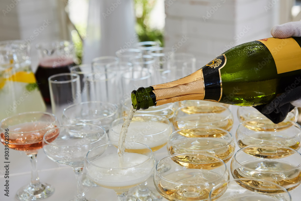Fototapety, obrazy: Pouring champagne in flutes standing on table