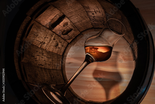 Photo a glass of whiskey in an oak barrel