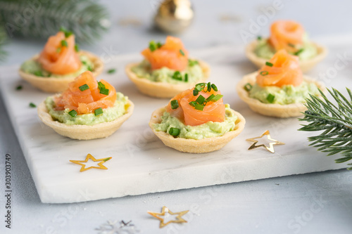 Fotografie, Obraz  Canapes with smoked salmon, cream cheese and avocado on light background with space for text