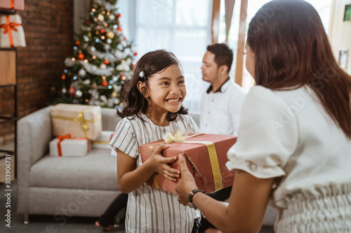 Fotografía  beautiful daughter giving her mom a present on christmas day celebration