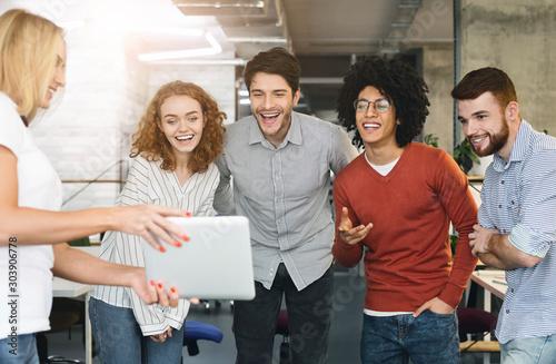 Obraz Young creative team attending video conference via digital tablet - fototapety do salonu