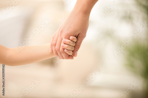 Obraz Mother holding hands with her child indoors, closeup. Happy family - fototapety do salonu