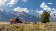 Deserted Wooden Barn On The Prairy With Mountains And A Cloudy Sky In The Background