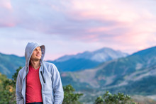 Aspen, Colorado Colorful Purple Blue Twilight Sunset Blurry Background View Of Rocky Mountains And Happy Young Man Standing Looking In Hoodie Sweater