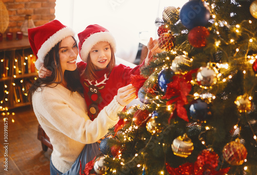 Obraz Mother and daughter decorating beautiful xmas tree - fototapety do salonu