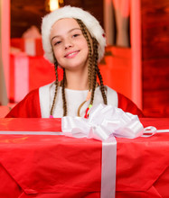 Portrait Kid With Gift. Winter Shopping Sale. Smiling Little Girl. Night Xmas. Delivery Christmas Gifts. Happy New Year. Child In Red Santa Hat. Red Is Color Of Christmas. Childhood Happiness