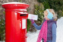 Young Girl In A Snow Covered Scene About To Post Her Christmas Letter To Santa