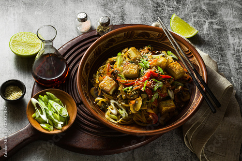 Fotomural  Asian vegan stir fry with tofu, rice noodles and vegetables, top view