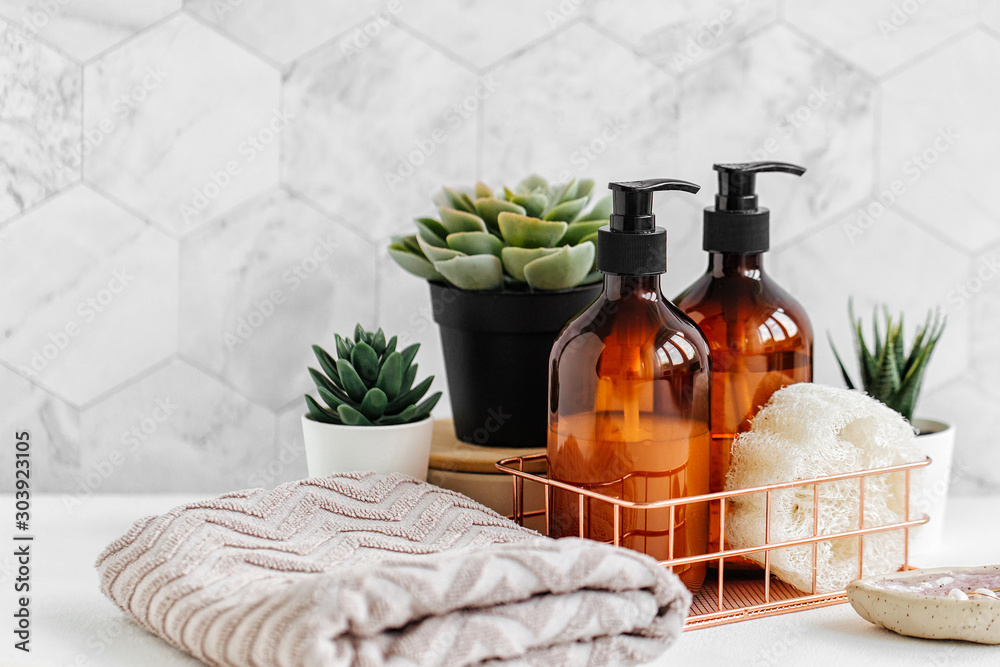 Fototapeta Soap and shampoo bottles and cotton towels with green plant on white table inside a bathroom background.