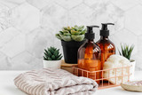 Soap and shampoo bottles and cotton towels with green plant on white table inside a bathroom background.