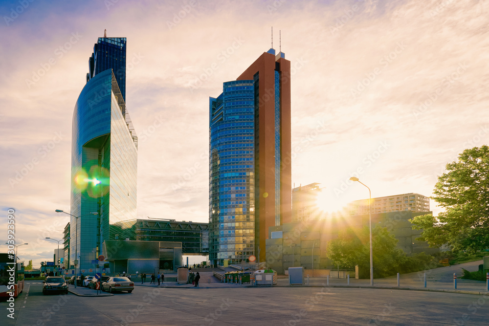 Fototapety, obrazy: Sunset at road and street with Glass Business office building architecture in Modern City in Vienna, Austria. Urban corporate skyscraper exterior and skyline. Blue windows design of Finance commercial