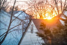 Golden Sunlight Sunset In Winter In Northern Virginia Residential Suburban Neighborhood With Bokeh Background Of Sky And Closeup Of House Roof