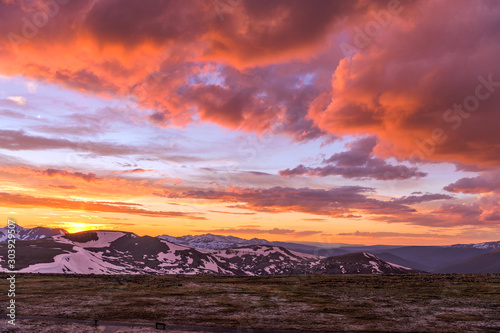 Foto auf Leinwand Hochrote Spring Sunset at Top of Rockies - A wide-angle view of colorful Spring sunset clouds over snow-capped high peaks of the Continental Divide at top of Rocky Mountain National Park, Colorado, USA.