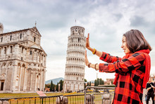 Funny Asian Girl Supporting Famous Leaning Tower In Pisa. Travel Concept