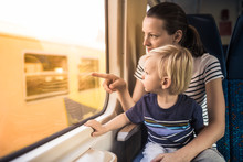 Mother And Child Riding On Train Together. Parenting And Teaching Your  Kids Concept.
