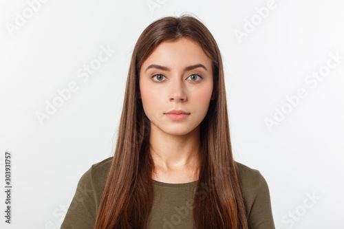 Obraz Portrait of a beautiful young woman looking at the camera and smiling, isolated on a white background. - fototapety do salonu