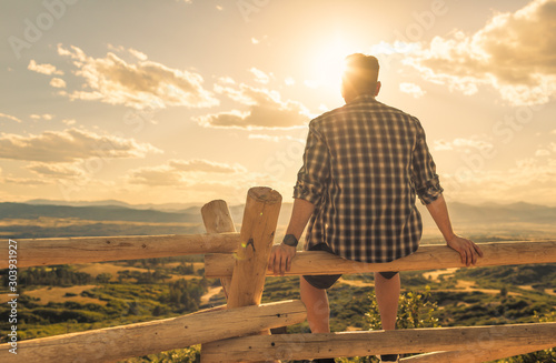 Obraz Thoughtful young man sitting in a peaceful nature setting.  - fototapety do salonu