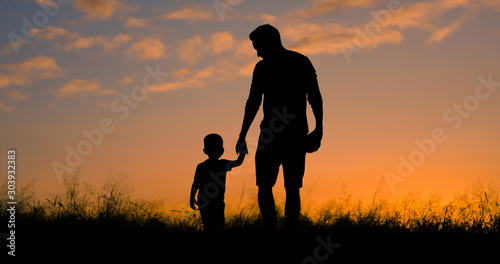 Obraz Loving father walking side by side with son holding hands.  - fototapety do salonu