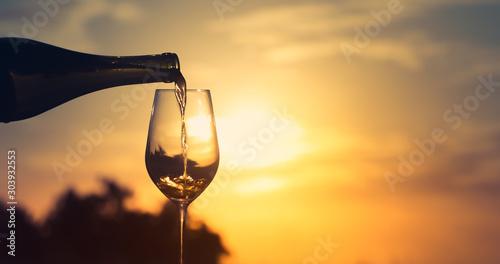 Fototapeta Wine pouring into glass on sunset background.  obraz