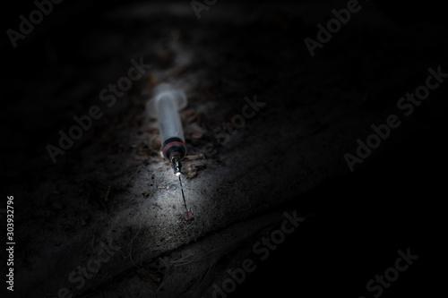 Fotografija  used disposable syringe thrown on the street, anti-drug, destructive addiction,