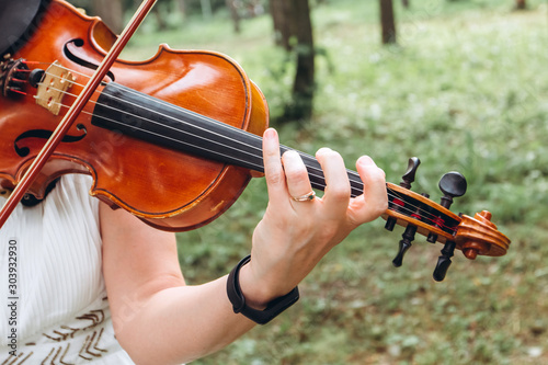 female musician performs at an outdoor wedding. Curl with the neck of the violin closeup. The actor performs at a party. musical instrument. Hands of a violinist close-up. - 303932930