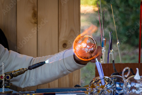 Photo Glassblower handling the glass ball with a gas burner