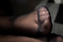 A Close Up Portrait Of A Foot In Black Nylon Pantyhose With A Reinforced Toe. The Details Of The Fabric Are Visible.