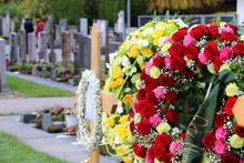 Ein Friedhof In Österreich, Blumenkränze An Einem Neuen Grab Nach Der Beisetzung, Im Unscharfen Hintergrund Der Friedhof