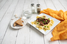 Beef Tips Over Bow Tie Pasta And Alfredo Sauce