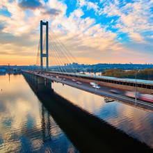 Automobile And Railroad Bridge In Kiev, The Capital Of Ukraine. Bridge At Sunset Across The Dnieper River. Kiev Bridge Against The Backdrop Of A Beautiful Sunset In Kiev. Bridge In Evening Sunshine