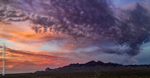 Sunset, aerial landscapes of Santa Rita Mountains from above Tubac, Arizona with warm , golden plains, purple mountains, blue sky with colorful clouds on a Fall day