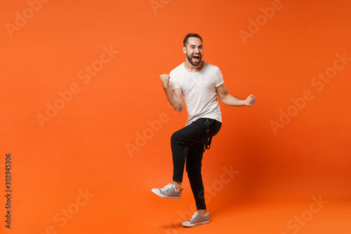 Fotografía  Joyful happy young man in casual white t-shirt posing isolated on orange wall background studio portrait