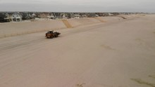Aerial Of Front Loader Carries Bucket Full Of Sand Driving Down Beach.